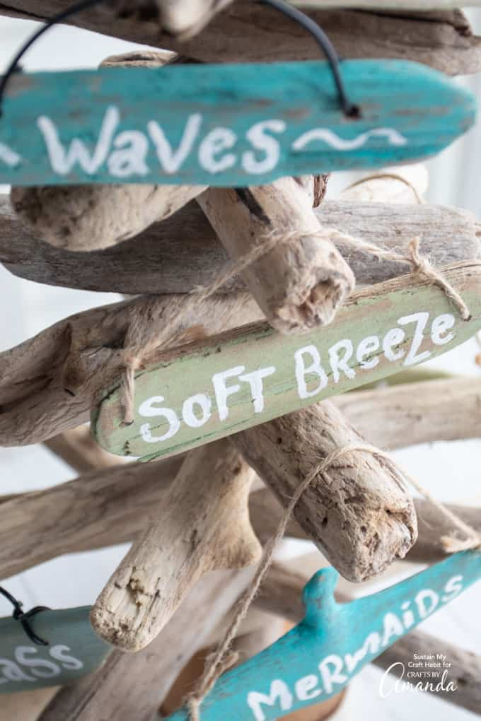 beach sign ornaments made from driftwood pieces hanging up