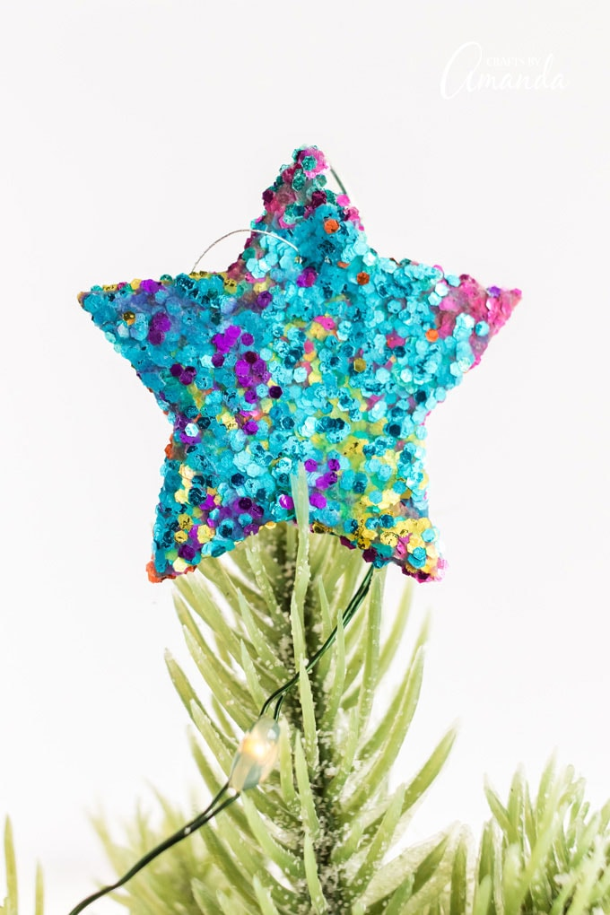 blue glittery star ornament on top of tree