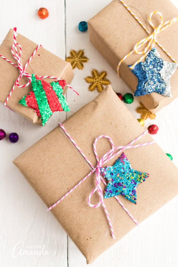 3 gift boxes tied with bakers twine and a star ornament on top of each