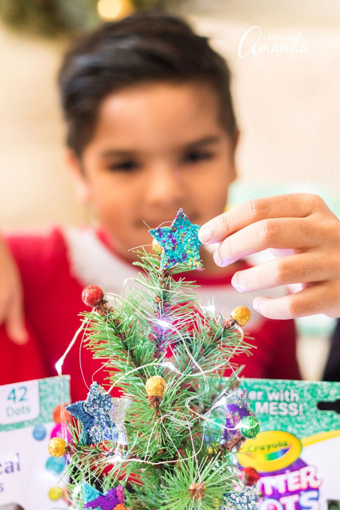 child placing star ornament on top of tree