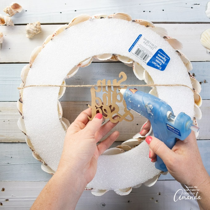 attaching wooden cut out sign to the back of the wreath