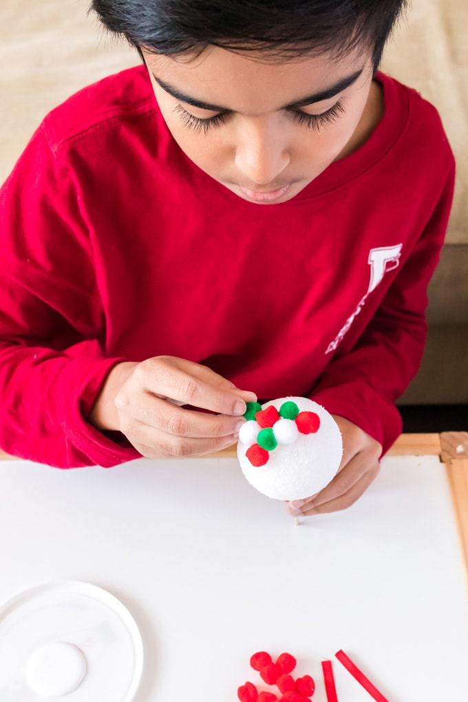 little boy gluing pom poms to styrofoam ball