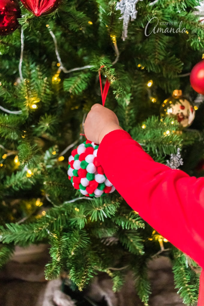little boy hanging ornament on christmas tree