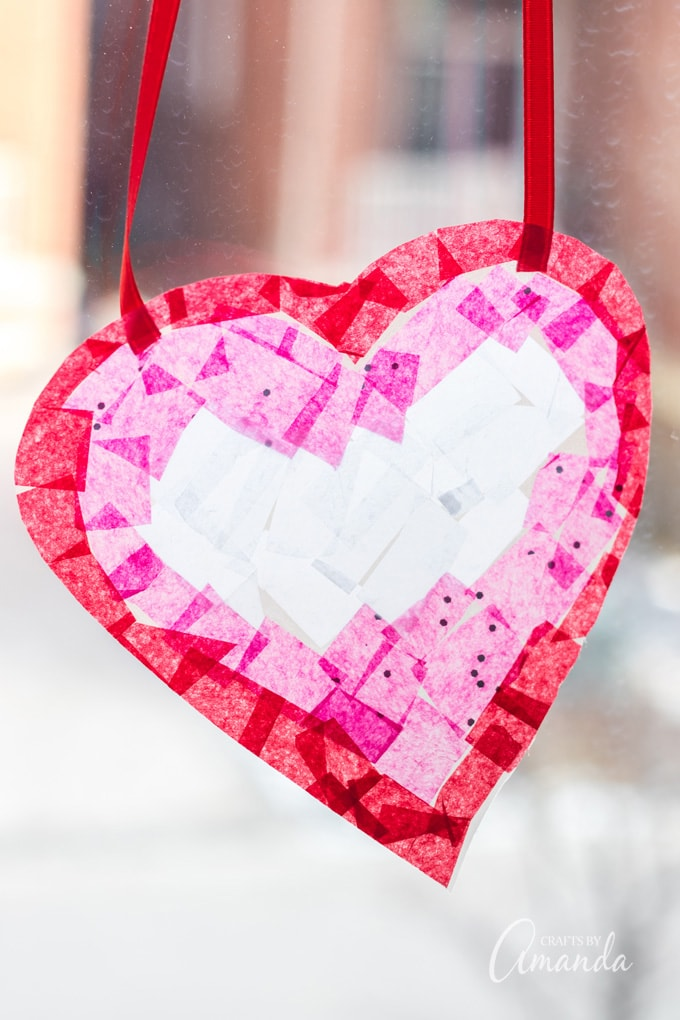 red, pink, and white heart shaped suncatcher made with tissue paper