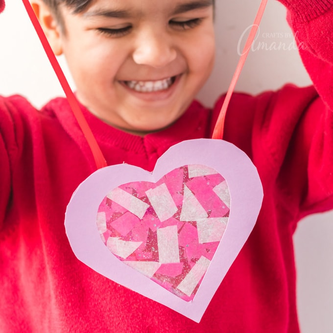 cute little boy holding Valentine's Day heart suncatcher