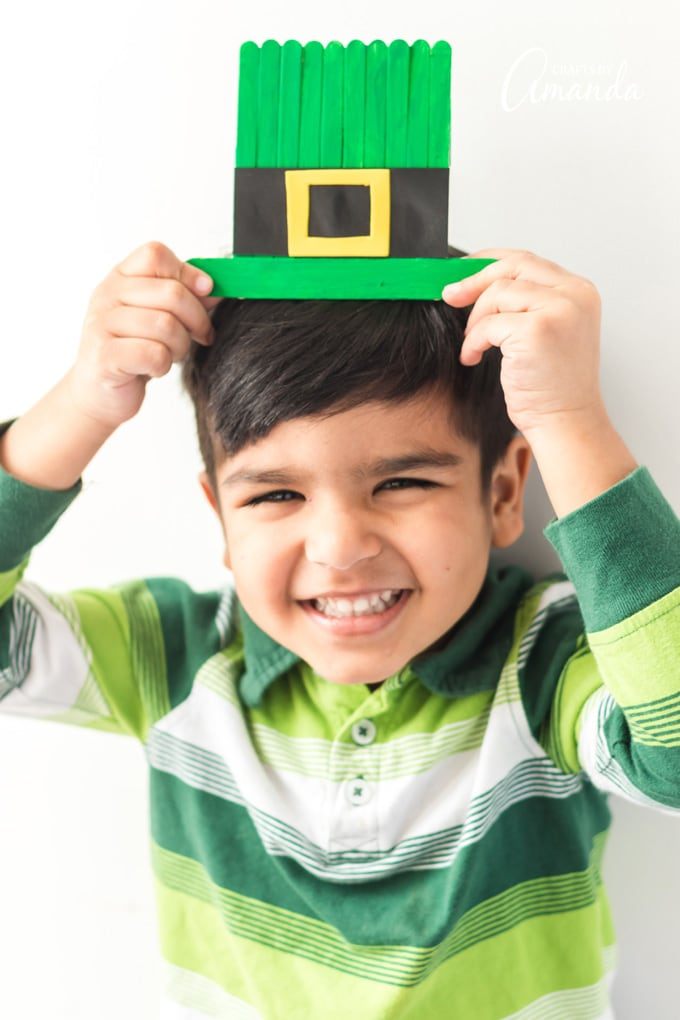 cute little boy holding craft stick leprechaun hat over his head