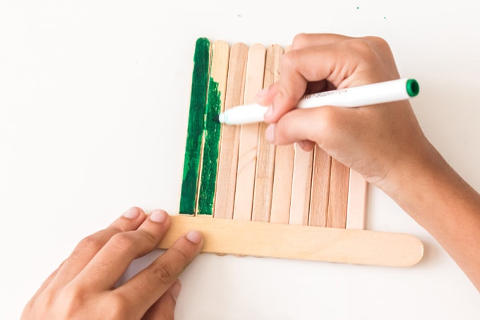 coloring craft sticks with a green marker