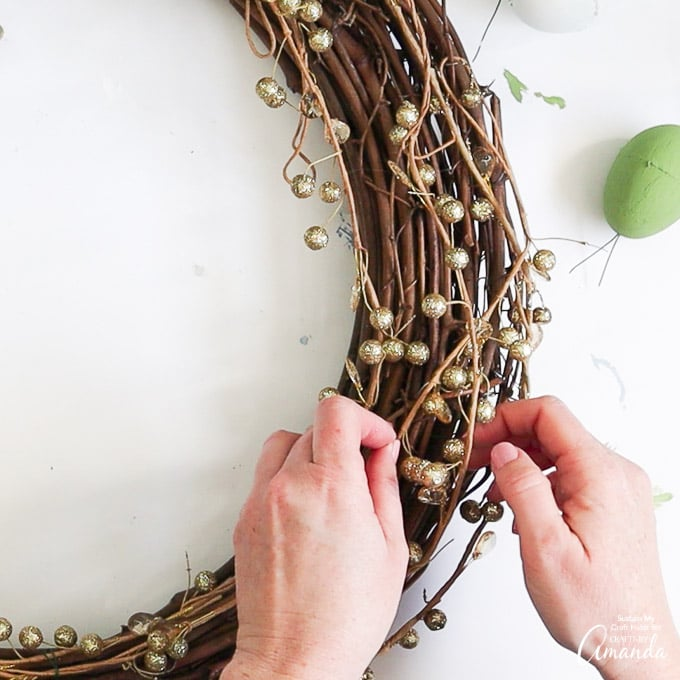 attaching glittery gold garland to grapevine wreath