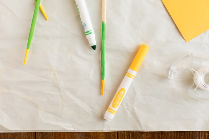 coloring a chopstick with green marker