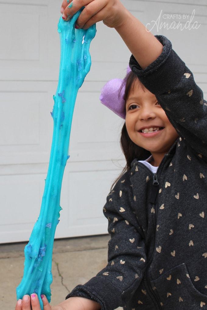 little girl stretching homemade mermaid slime
