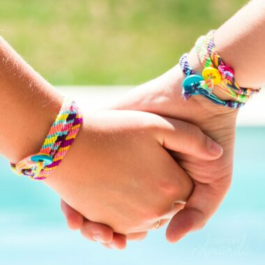 two girls holding hands wearing embroidery floss bracelets