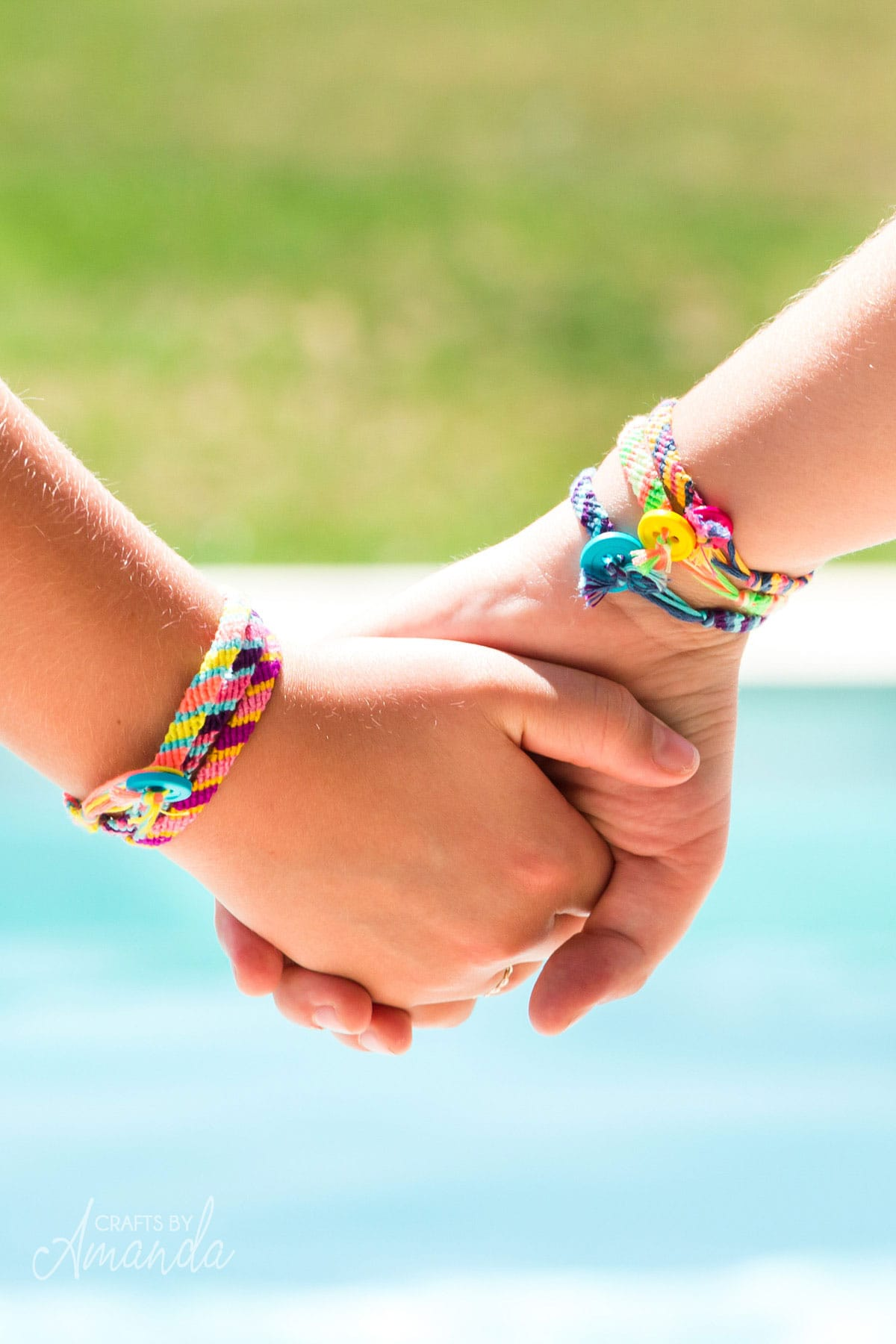 two girls holding hands wearing friendship bracelets