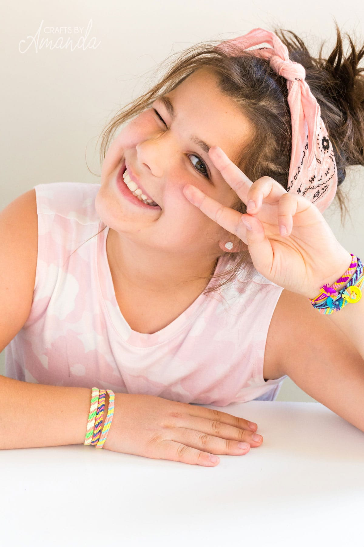 little girl wearing a friendship bracelet and making a peace sign