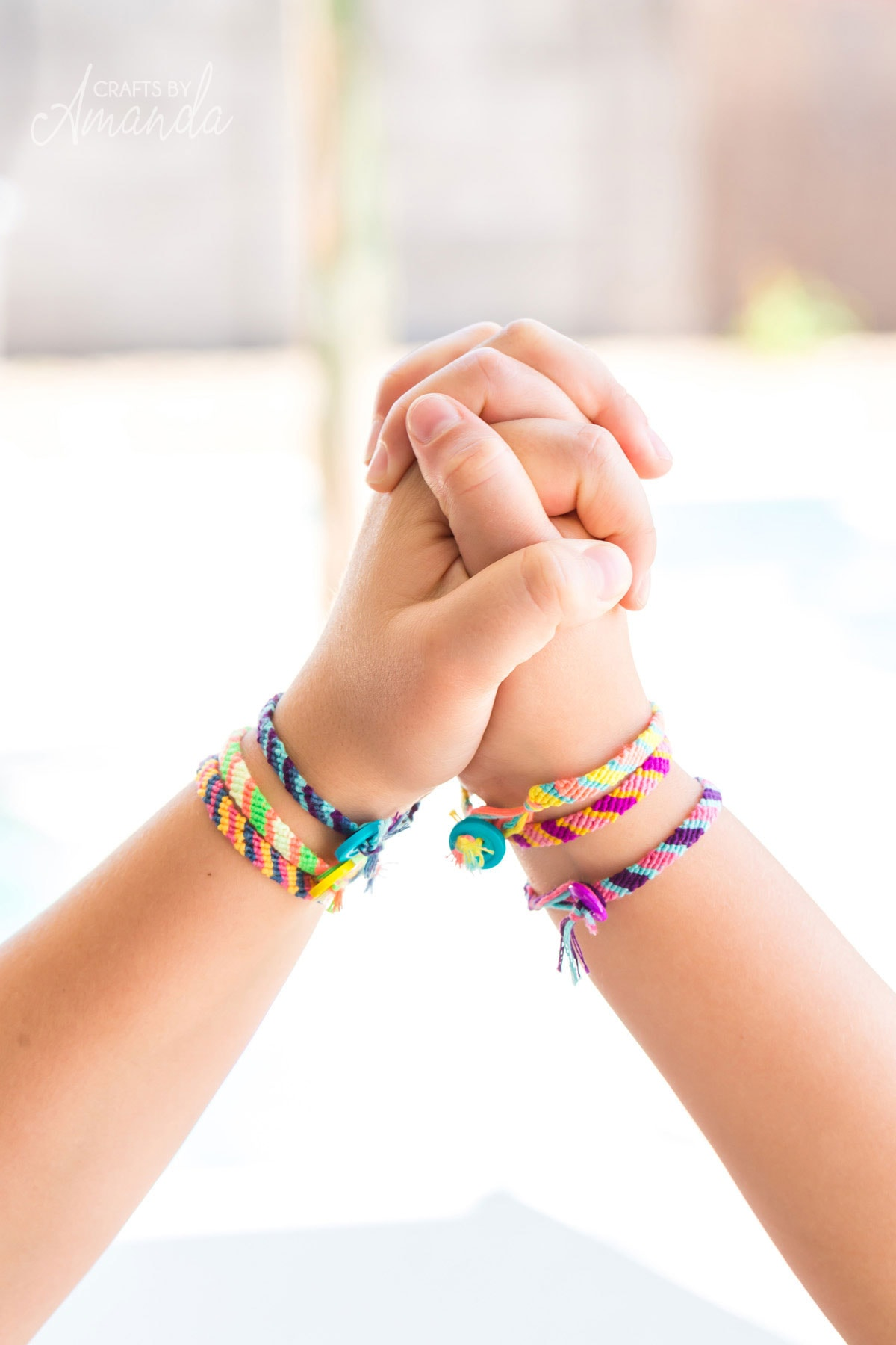 two girl's holding hands wearing the friendship bracelets they made