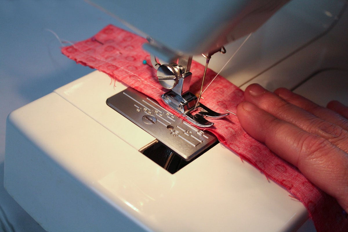 sewing a piece of fabric on a sewing machine