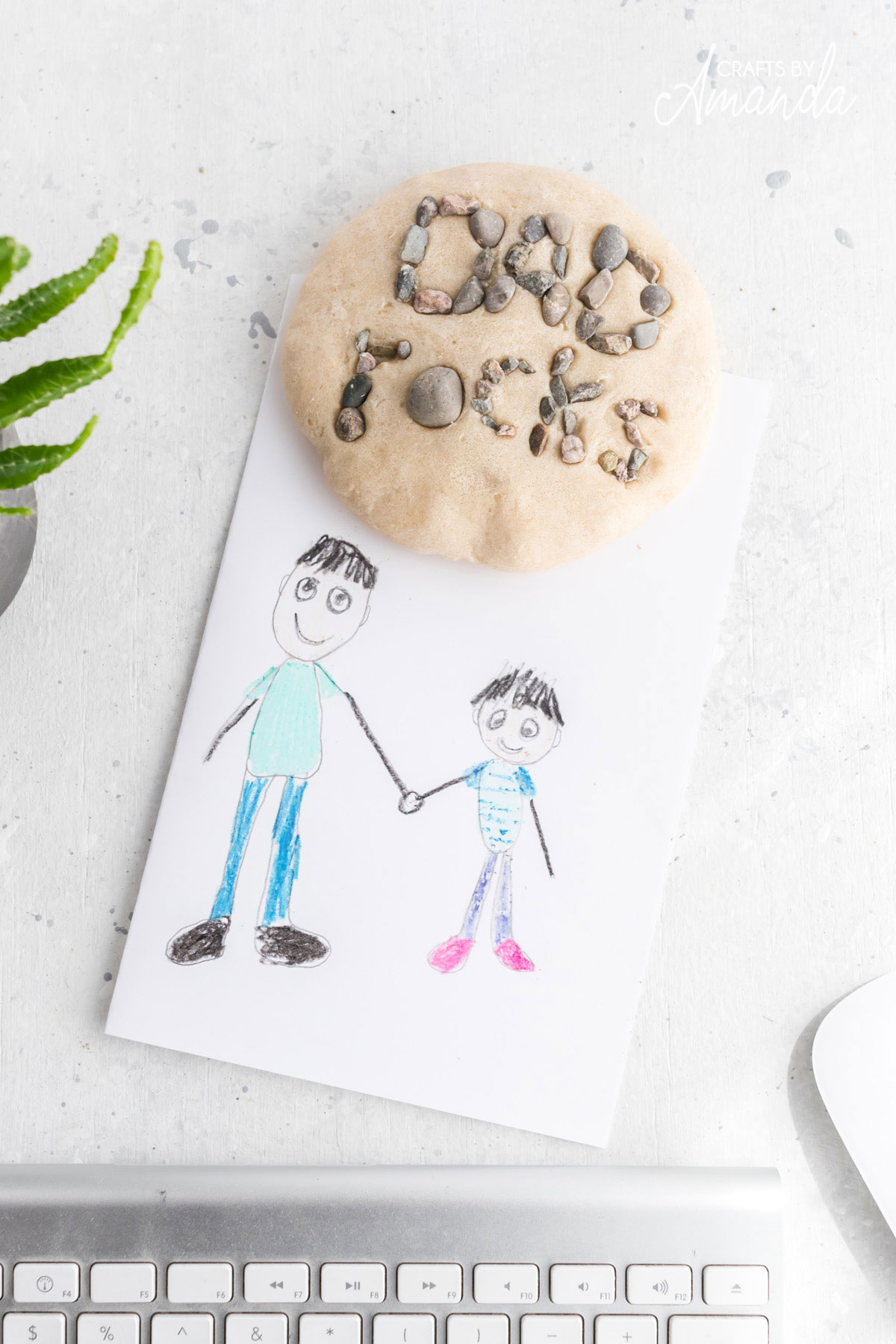 dad rocks paperweight on a desk with a cute drawing by a child