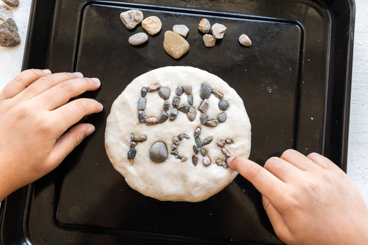 child spelling out dad rocks with gravel on a salt dough paperweight