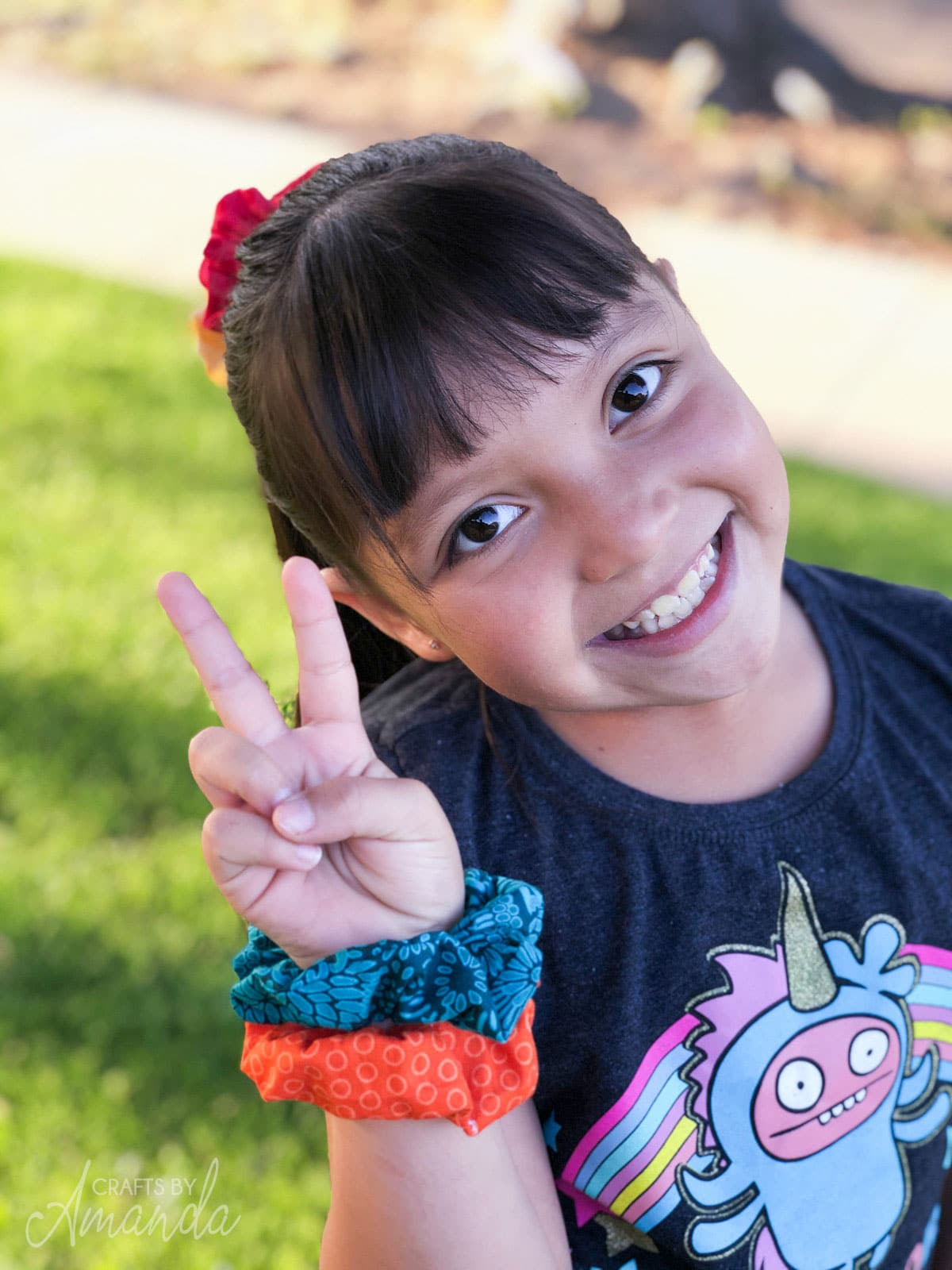 little girl smiling giving peace sign with scrunchies on her wrist