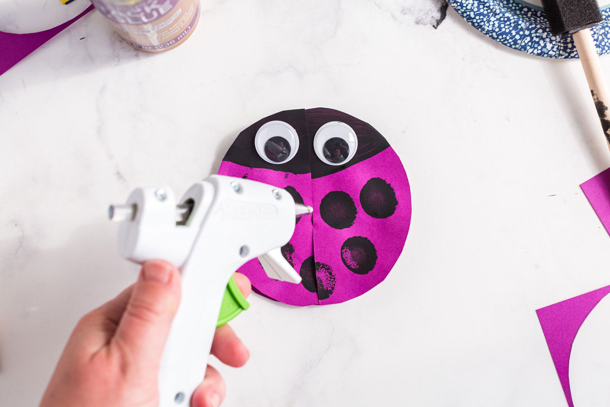 child holding glue gun over paper ladybug