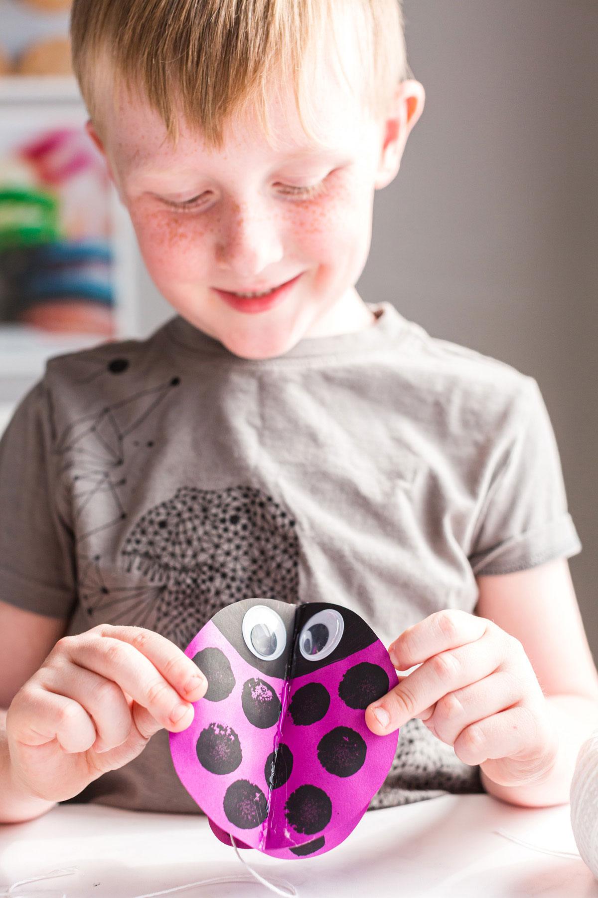 child holding twirling paper ladybug