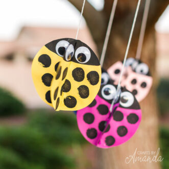 paper ladybugs hangig from tree blowing in the wind