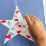 child adding tissue paper pieces to star on contact paper