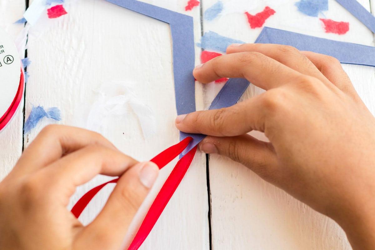 child tying ribbon