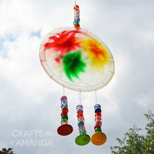 plastic lid suncatcher hanging in window