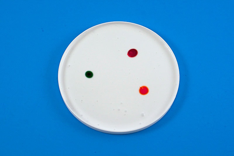 plastic lid filled with glue and three dots of food coloring