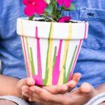 little boy holding drip paint pot