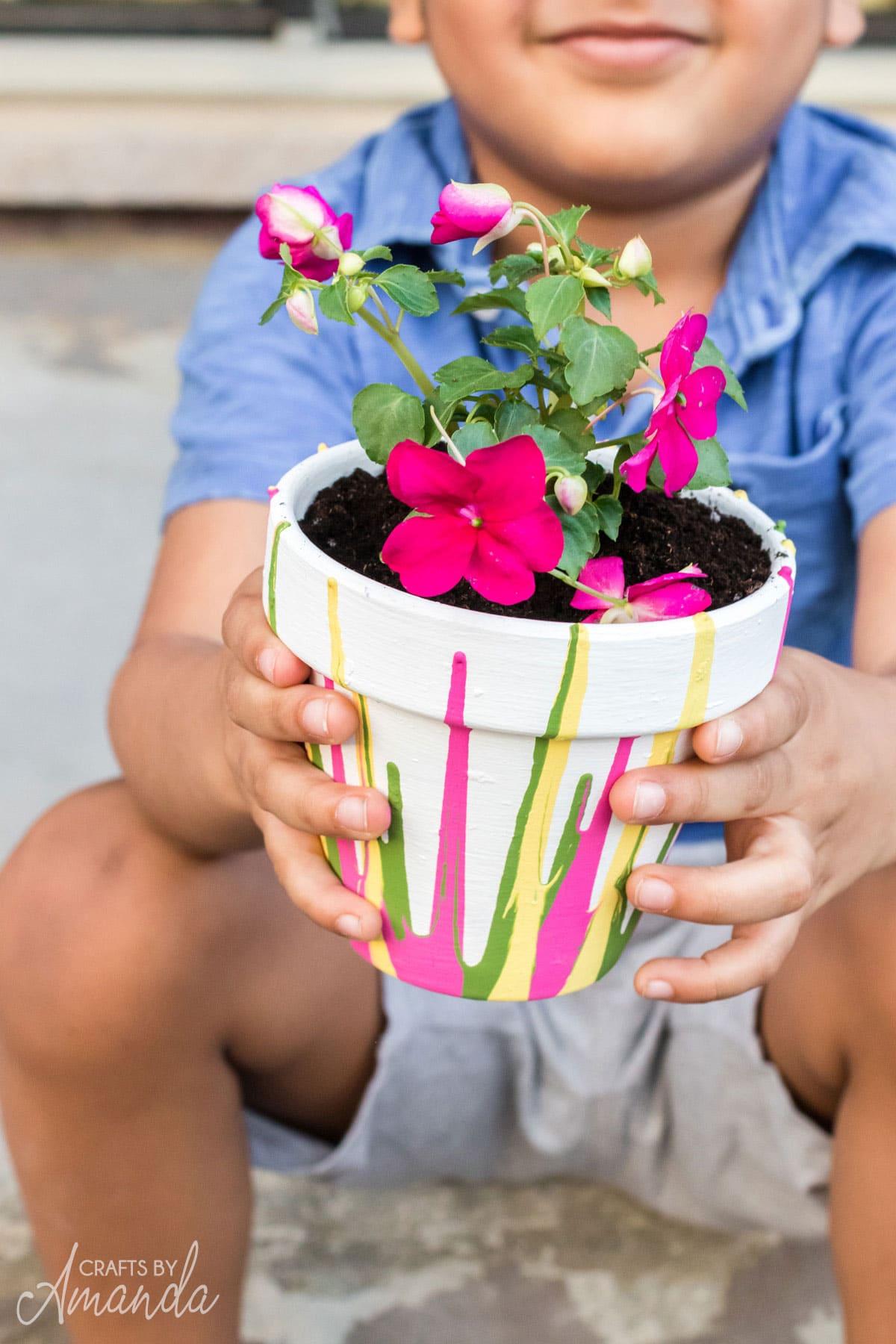 little boy holding a pot of flowers