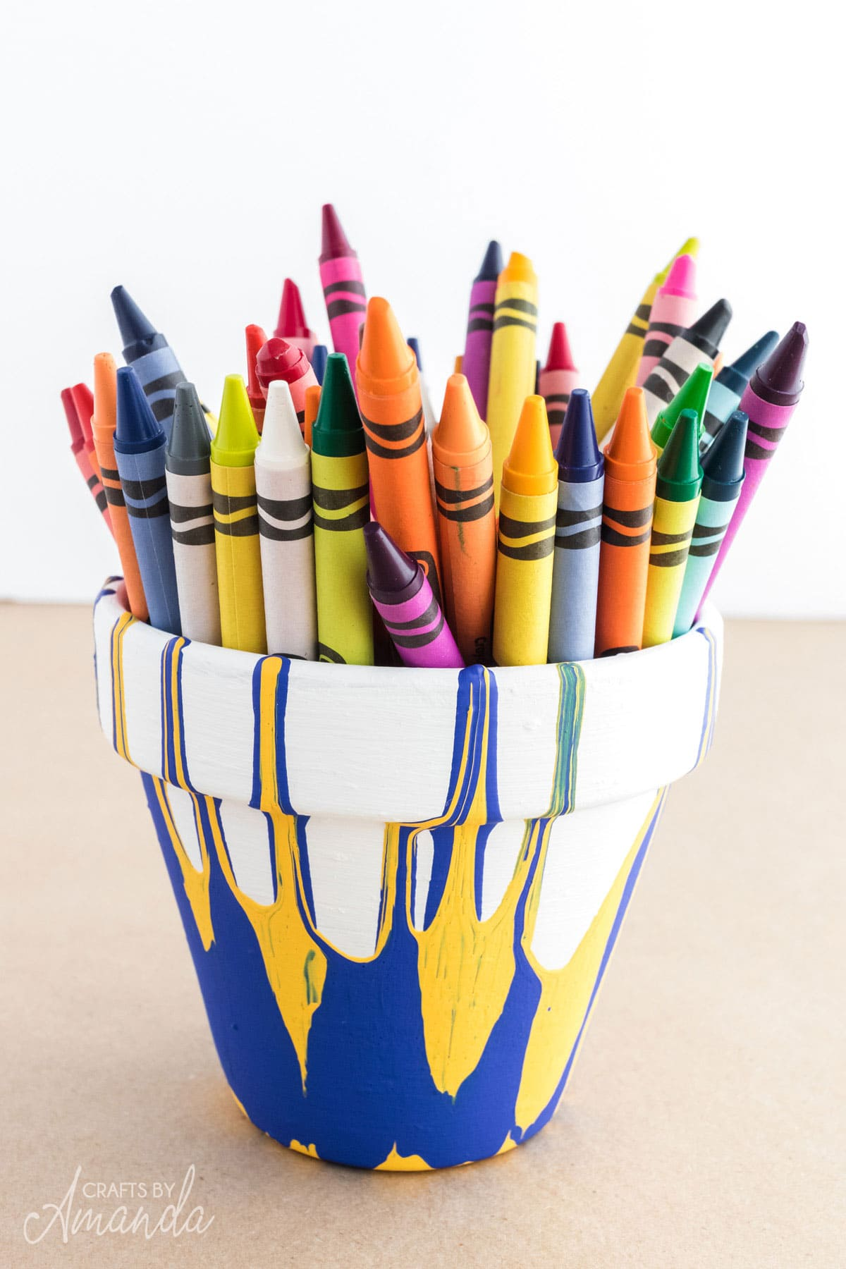 drip painted pot filled with crayons