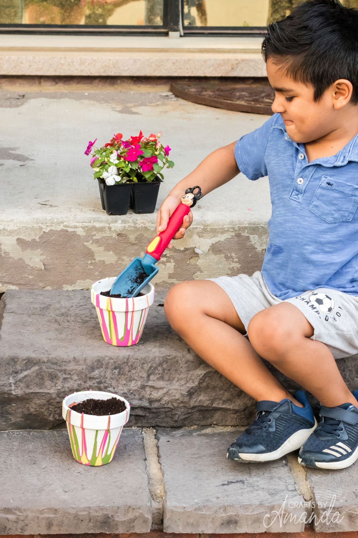 child scooping potting soil into a pot