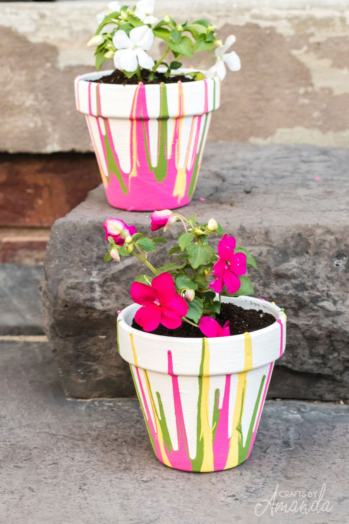 two drip painted pots with flowers on stairs