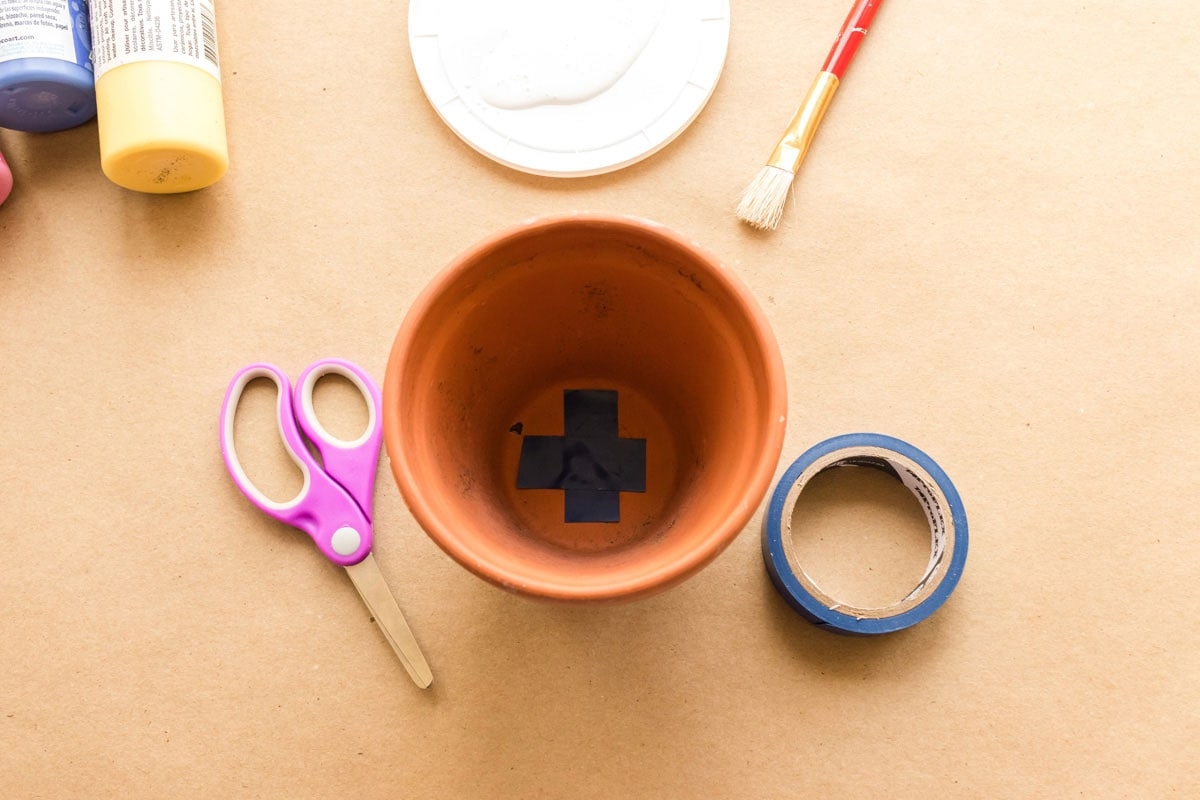 clay pot with blue tape over bottom hole