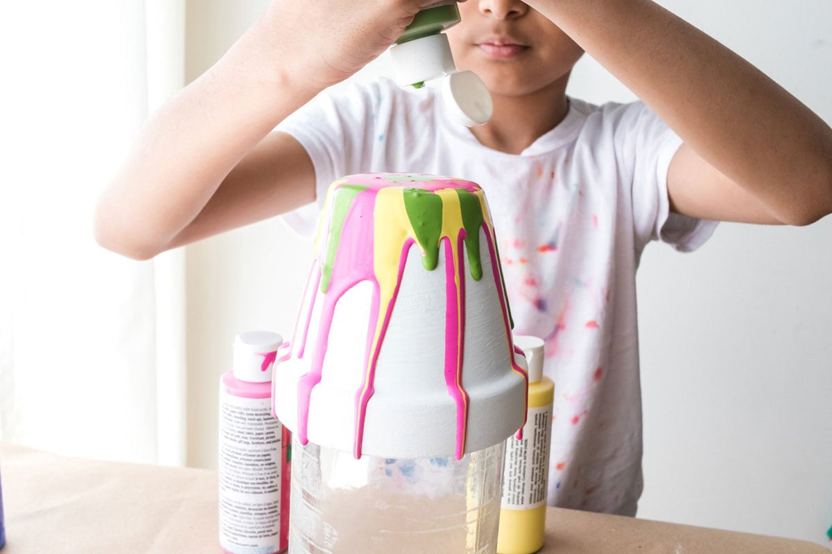 child squeezing green paint over yellow and pink paint