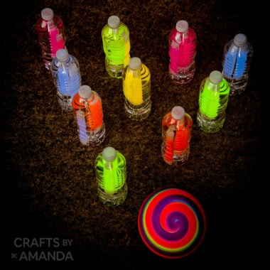 water bottles with glow sticks set up like bowling pins