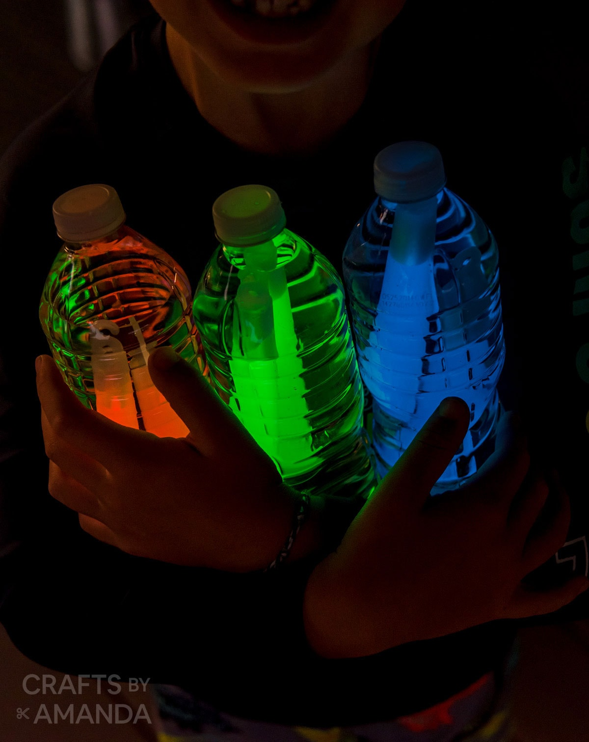 boy holding water bottles with glow sticks in them