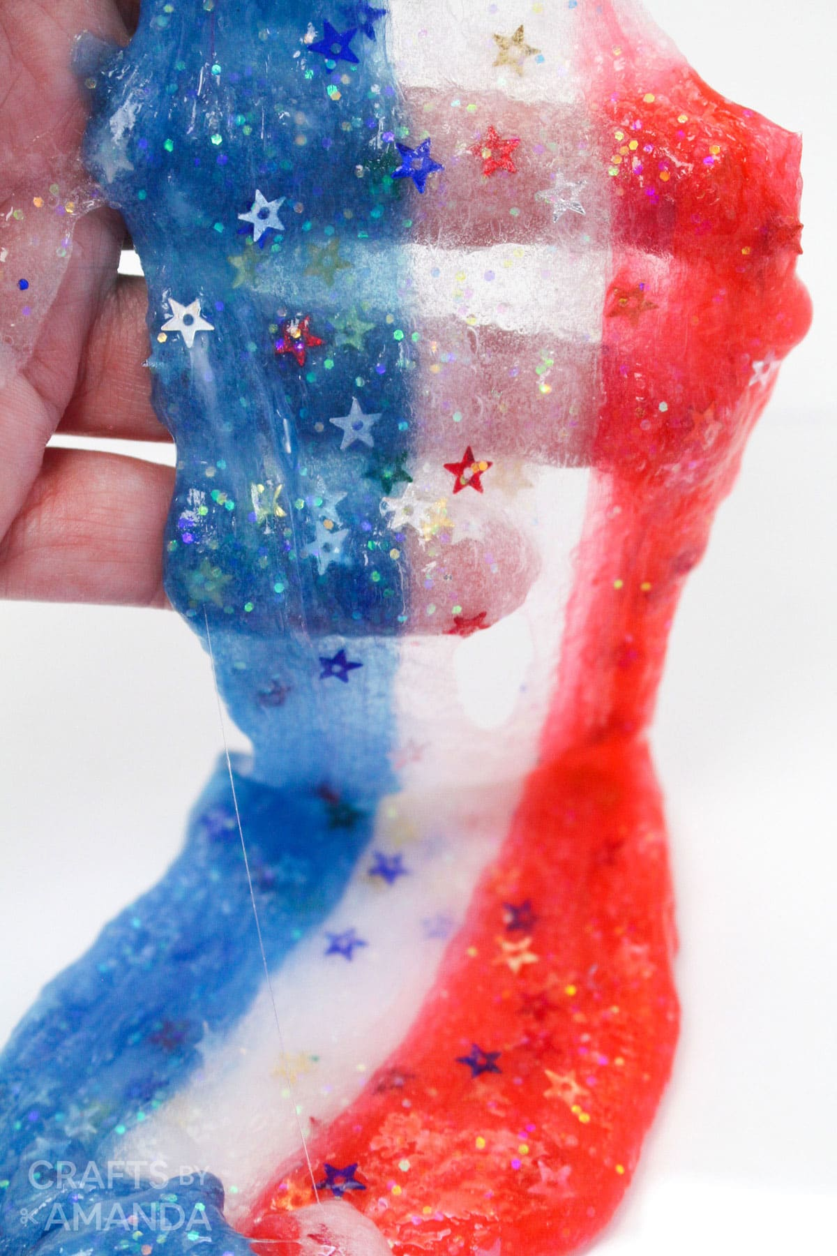 hand holding red, white, and blue slime