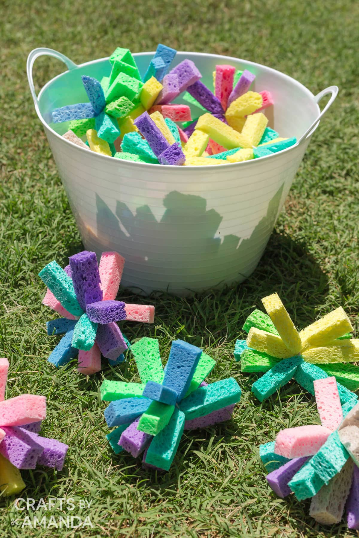 BUCKET OF SPONGE BOMBS SITTING IN THE GRASS