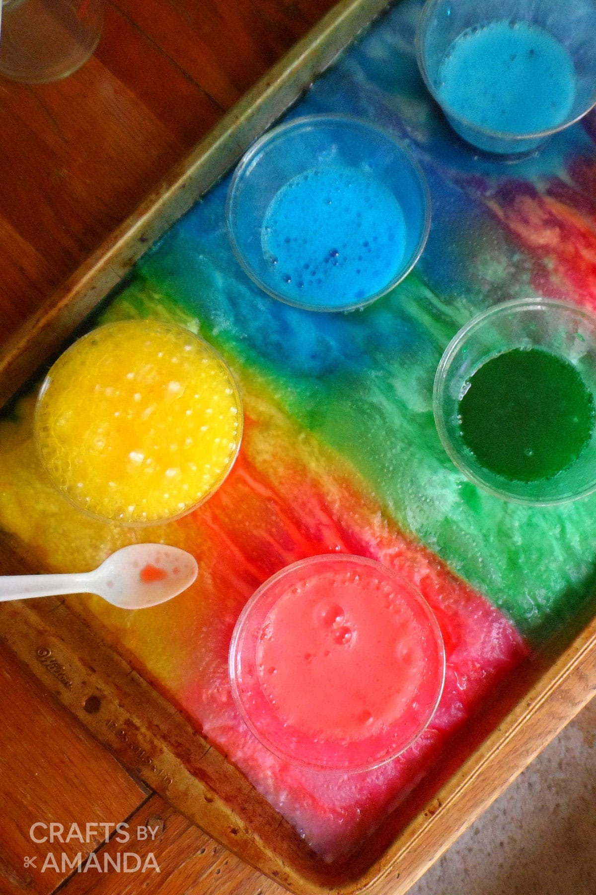 tray of plastic cups with food coloring, vinegar and baking soda