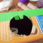 hole in cereal box with duck tape on it