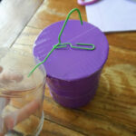 paper clips poked into plastic cup