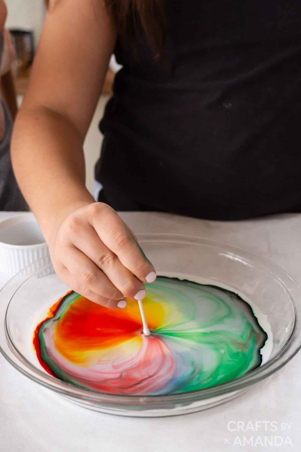 girl putting a q-tip into dish with milk and food coloring