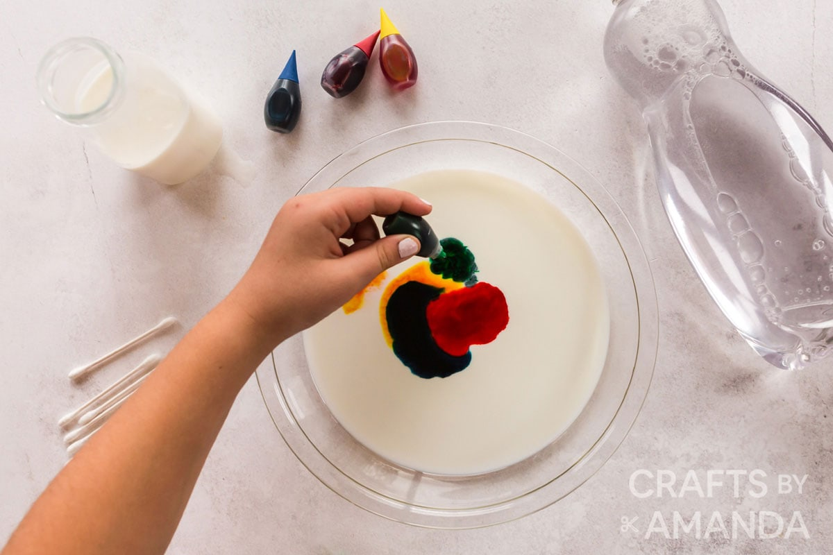 adding food coloring to milk