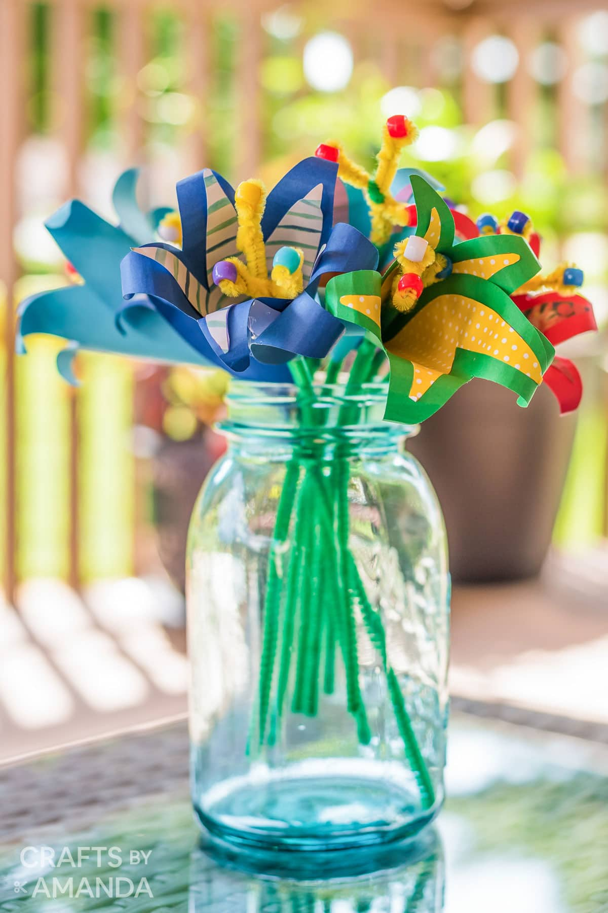 blue mason jar vase holding tropical paper flowers