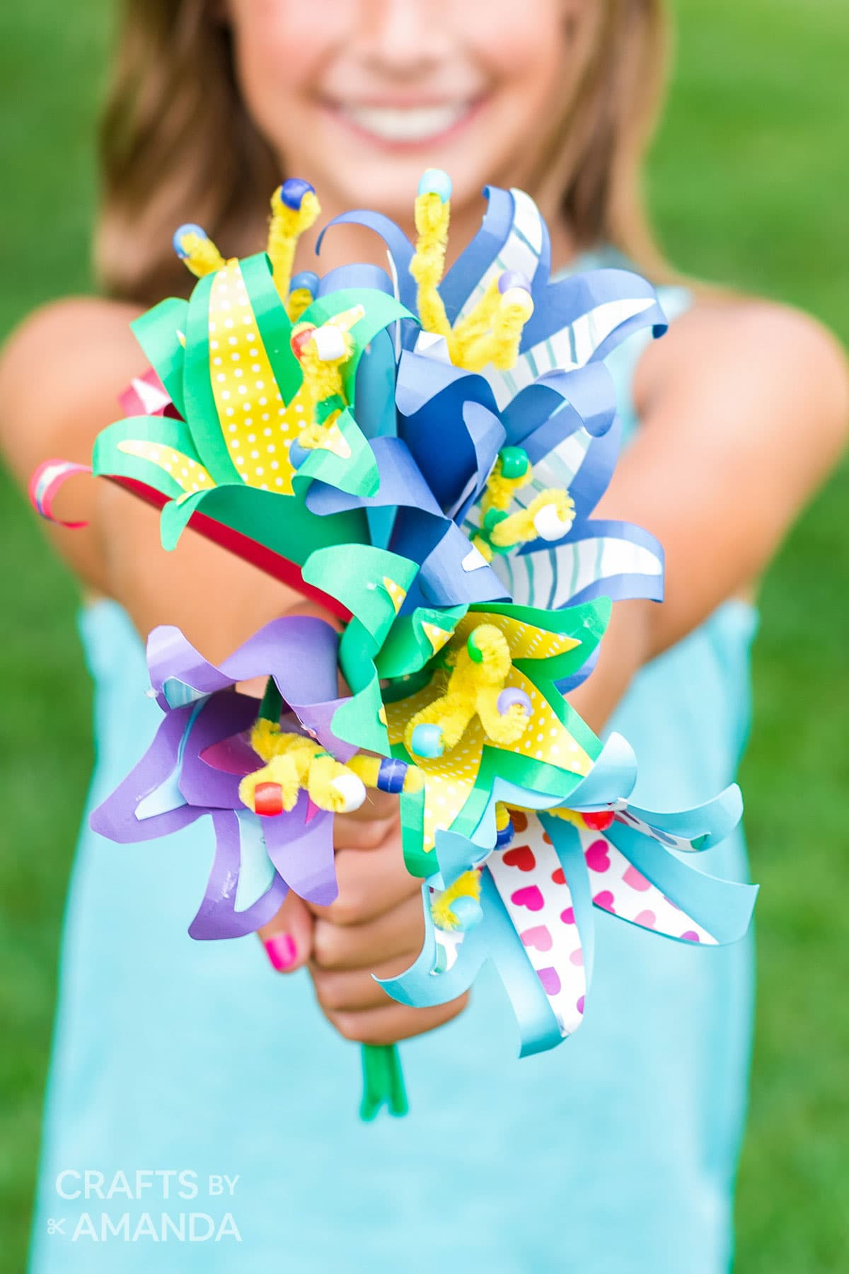 little girl holding bouquet of paper flowers