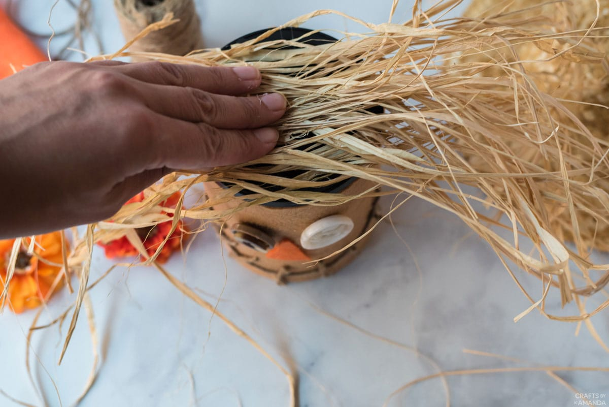 glueing raffia to top of coffee can