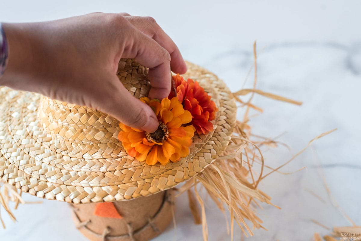 adding silk flowers to straw hat