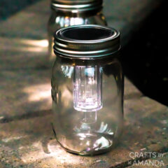 3 mason jar solar lights on a firepit ledge